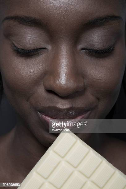 Close up of black woman eating bar of white chocolate