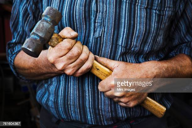 Close up of blacksmiths hands gripping a large hammer.