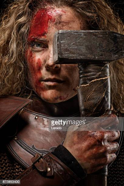 Close up of blonde bloody viking warrior female in studio shot