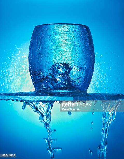 Close up of blue glass, ice cubes and dripping water