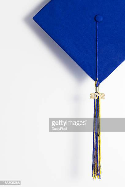 Close up of blue graduation cap hanging on white wall