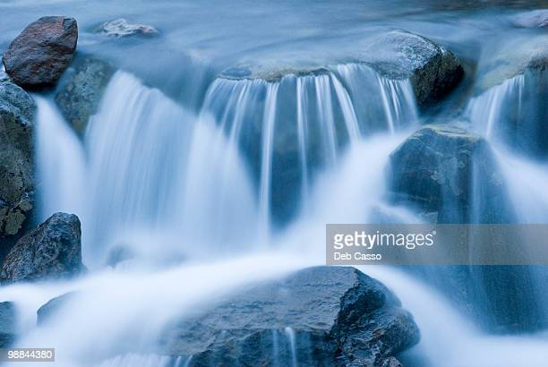 close up of blurred water rushing in stream - stream flowing water stock photos and pictures