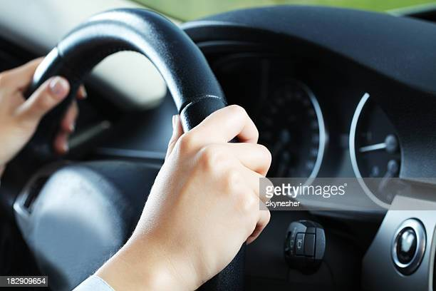 Close up of body part - hands on the wheel.