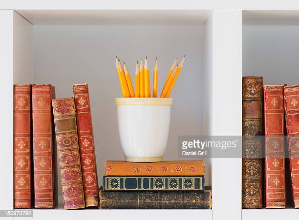 Close up of books and pencils on shelf, studio shot