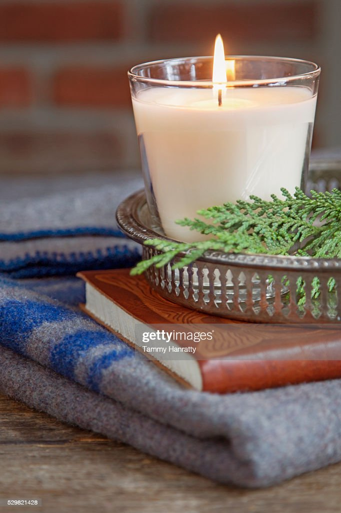 Close up of books, candle and woolen blanket : Stock-Foto