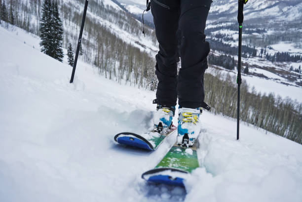 Close up of boots and skis while person skins uphill in Colorado.