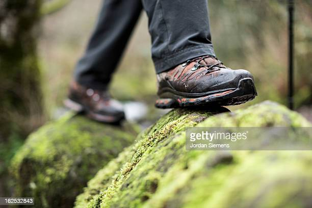 Close up of boots on a mossy rock.
