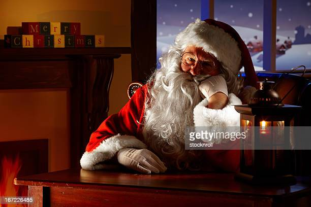 close up of bored santa sitting in his grotto - santa close up stock pictures, royalty-free photos & images