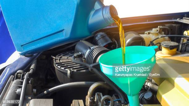close up of bottle pouring oil in engine - motor oil stock pictures, royalty-free photos & images