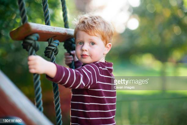 close up of boy 3-4 years old climbing ladder on playlet in backyard - 4 5 years stock pictures, royalty-free photos & images