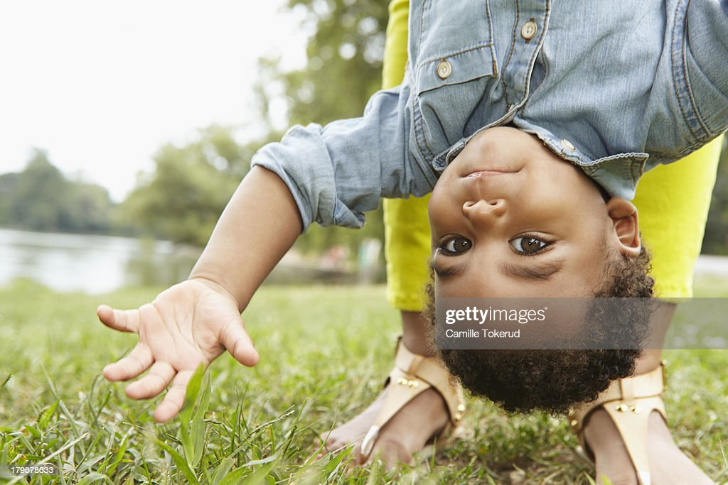 Close up of boy being held upside down by mother : Stock Photo