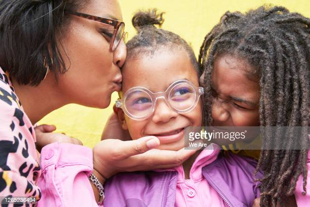 close up of boy being kissed by mother and brother - {{ collectponotification.cta }} stock pictures, royalty-free photos & images