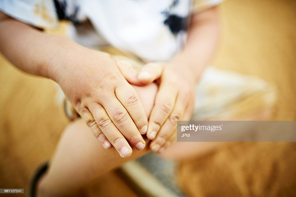 Close up of boy holding his knee with his hands : Stock Photo