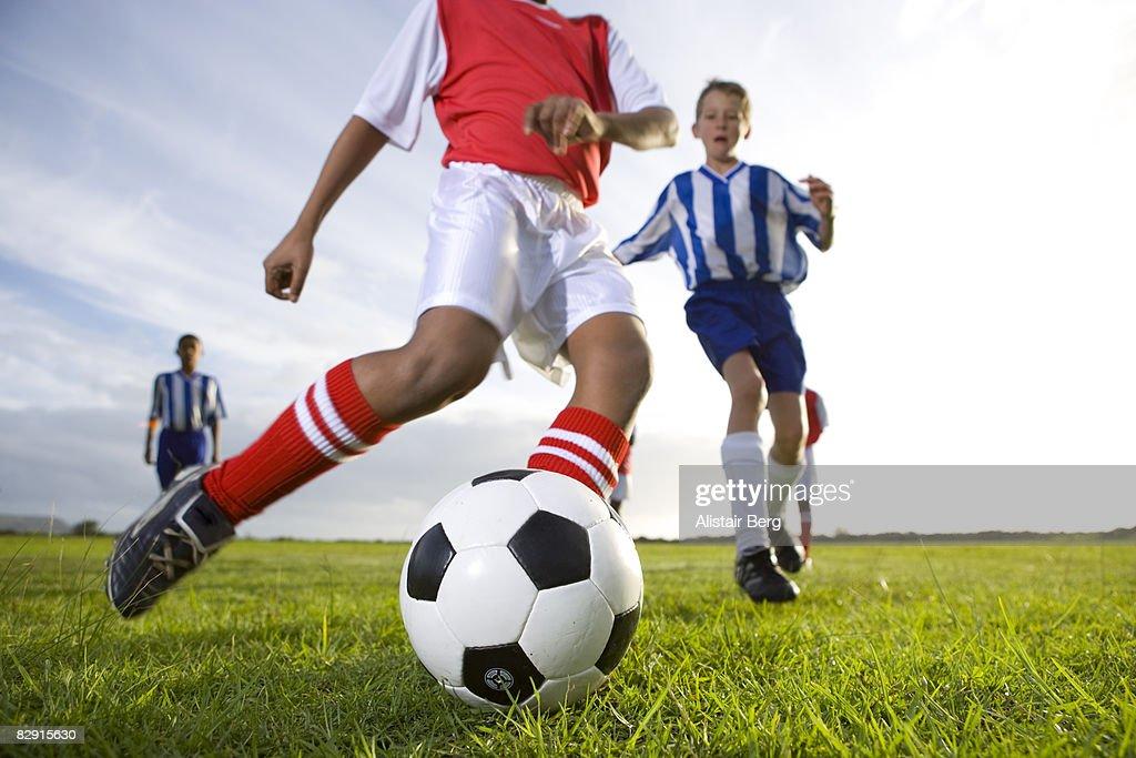 Close up of boy kicking football : Stock Photo