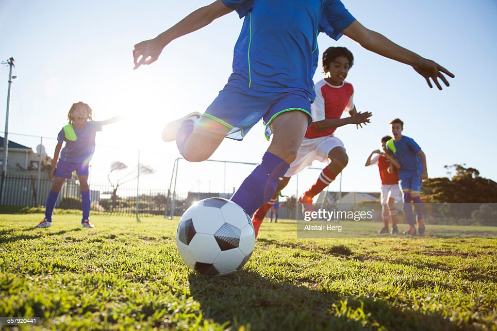 Close up of boy kicking soccer ball : Stock Photo