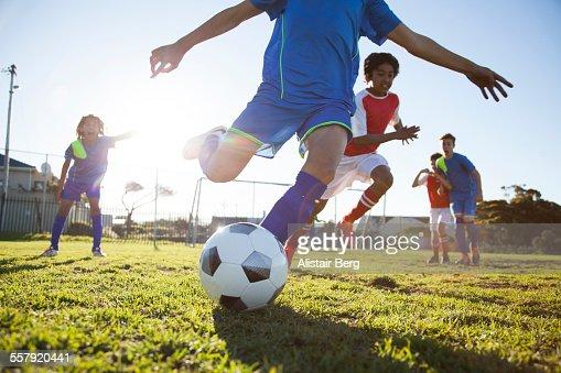 Close up of boy kicking soccer ball