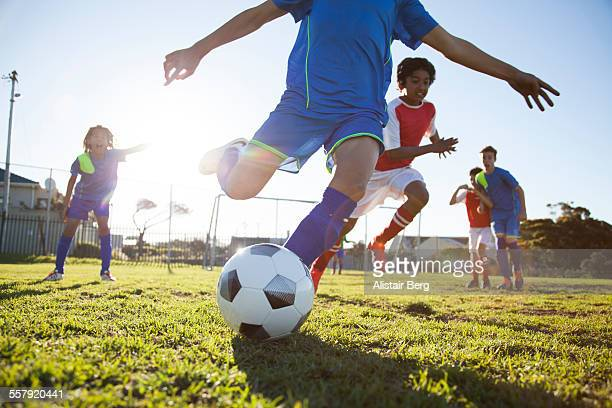 close up of boy kicking soccer ball - spielen stock-fotos und bilder