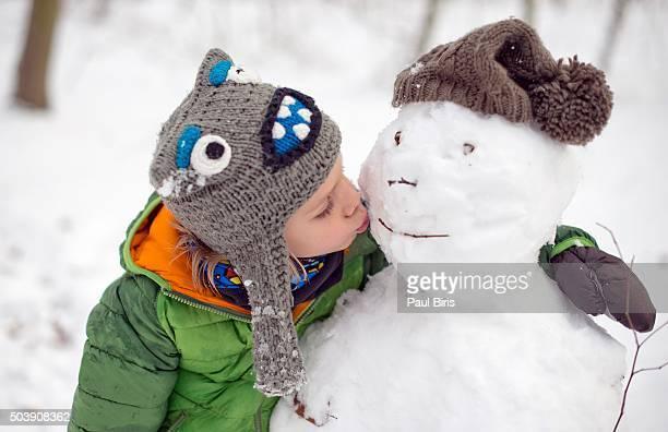 Close up of boy kissing snowman