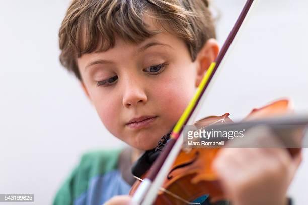 Close up of boy playing violin