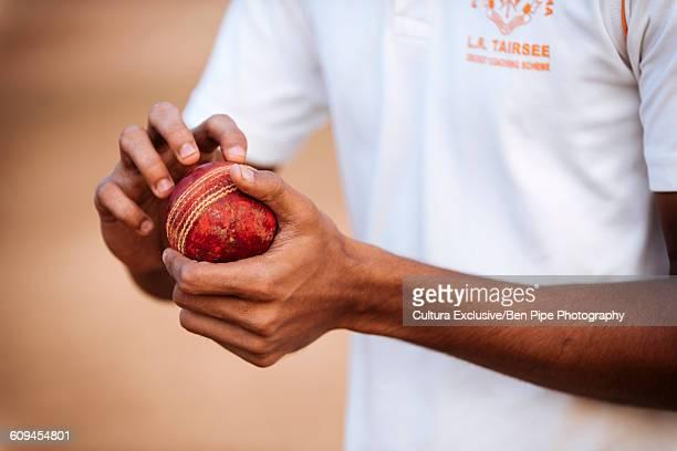 Close up of boy polishing cricket ball at Oval Maidan, Mumbai, India