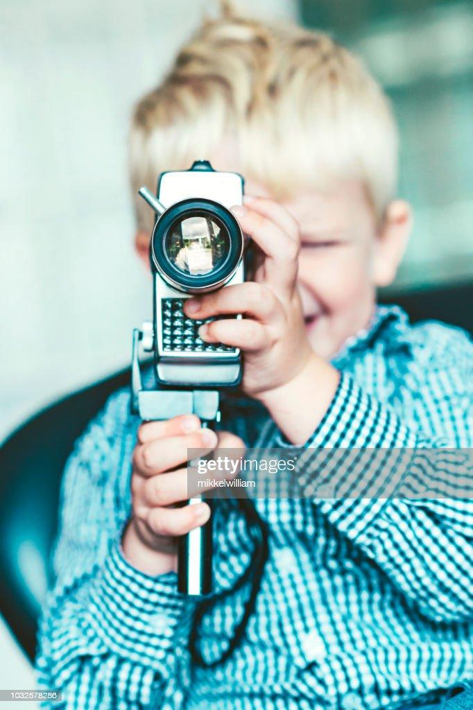 Close up of boy recording movie with retro 8mm video camera : Stock Photo