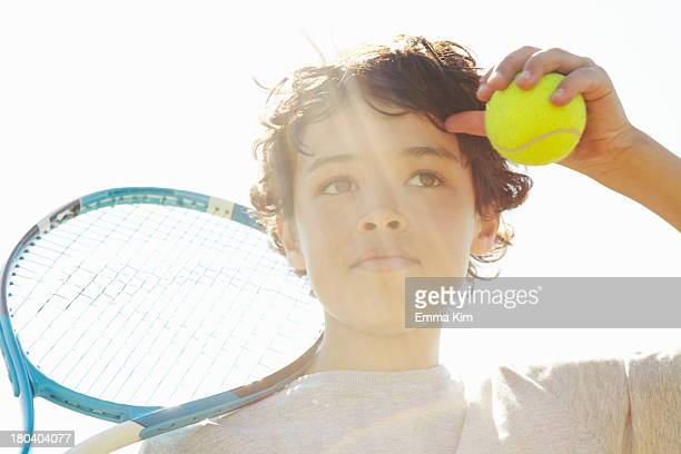 Close up of boy with tennis racket and ball