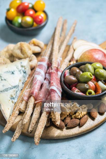 close up of breadstick, prosciutto, olives and blue cheese. - italian culture stock pictures, royalty-free photos & images