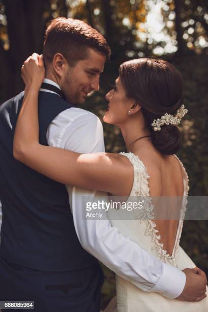 Close up of bride and groom looking at each other eyes , forest background