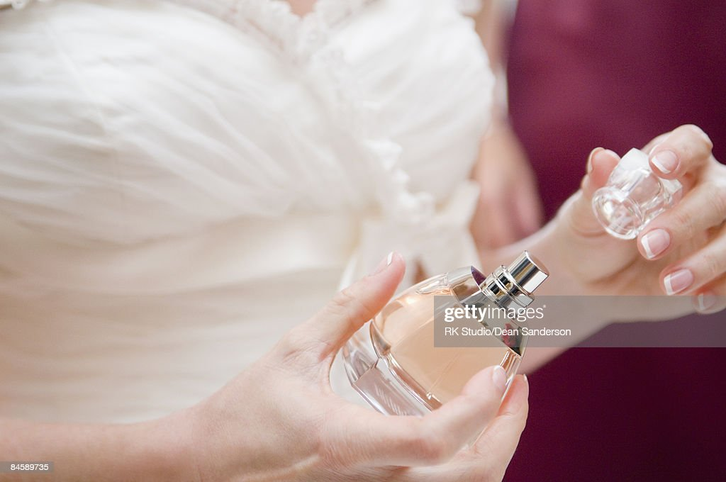 Close up of bride taking top off perfume bottle.  : Stock Photo