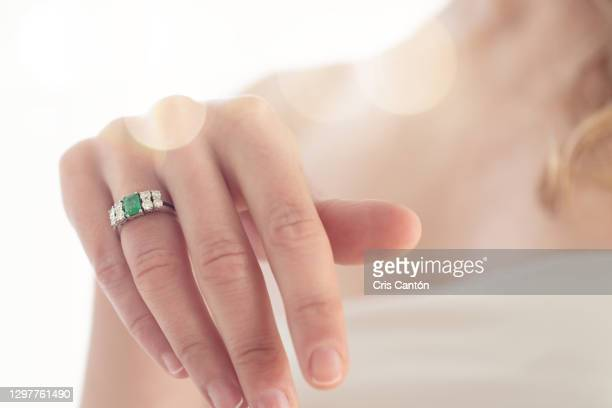 close up of bride with engagement ring with diamonds and emerald - cris cantón photography fotografías e imágenes de stock