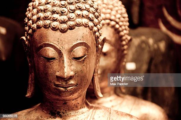 Close up of bronze Buddha statues.