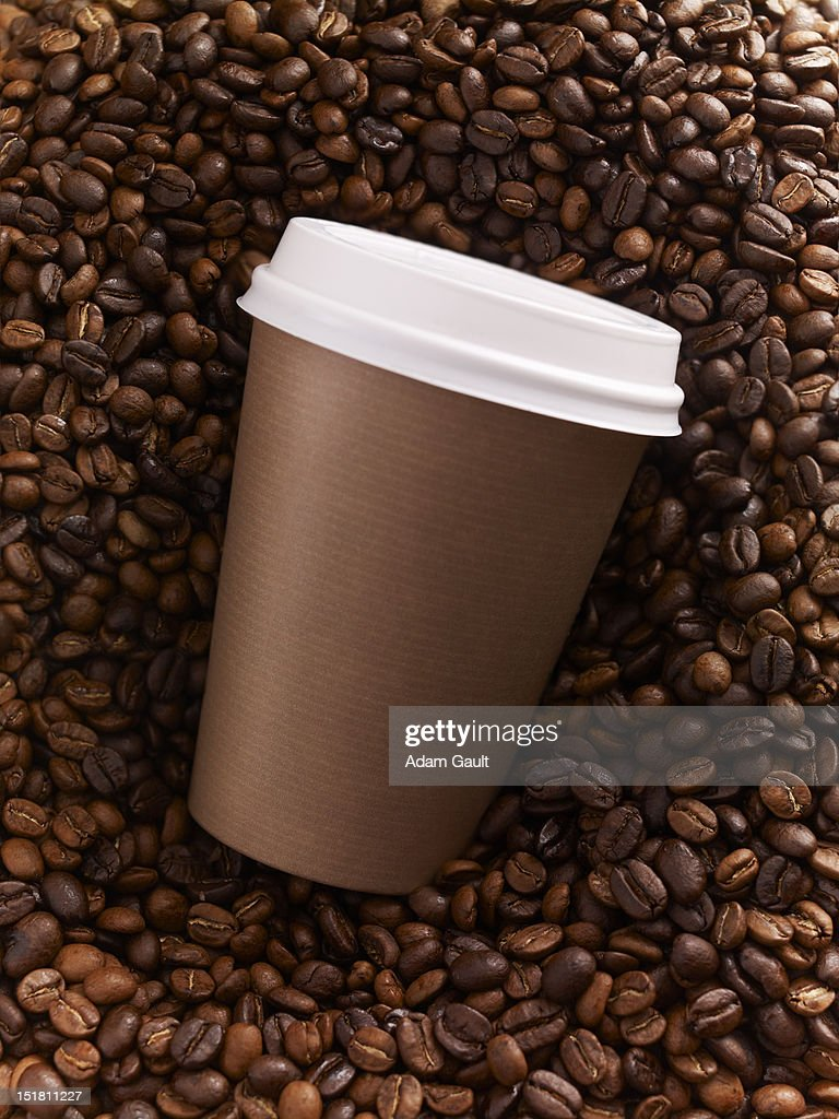 Close up of brown coffee cup on top of coffee beans : Stock Photo