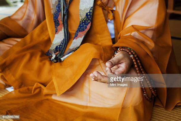 close up of buddhist monk wearing golden robe sitting cross legged on the floor, meditating, buddhist hand gesture. - shingon buddhismus stock-fotos und bilder