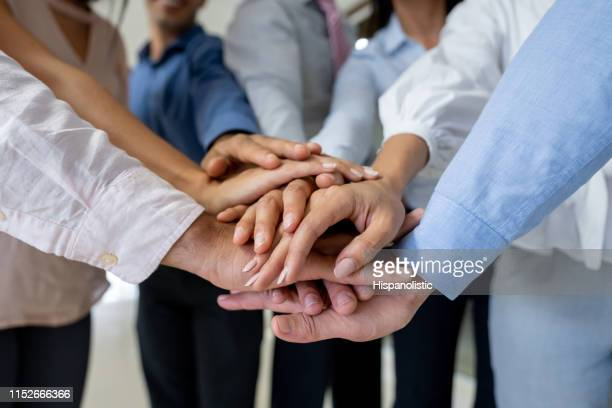 close up of business group in a huddle all with hands in - hispanolistic stock photos and pictures