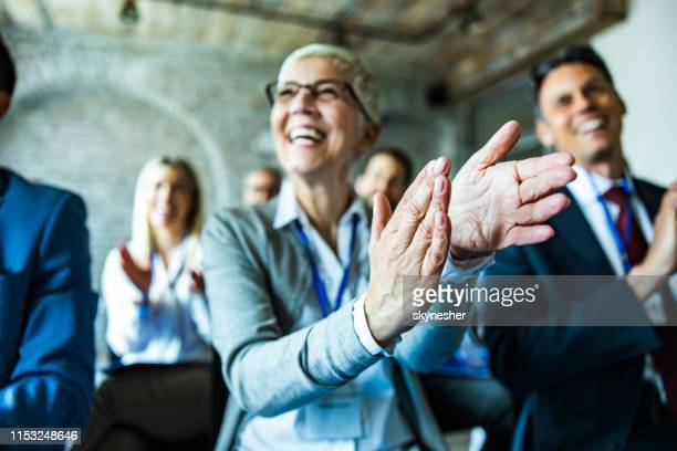 close up of business people applauding on a seminar in board room. - conferenza di lavoro foto e immagini stock