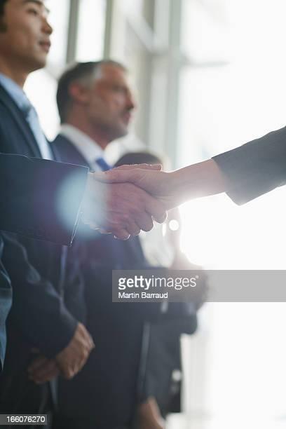 close up of business people shaking hands in a row - formele zakelijke kleding stockfoto's en -beelden