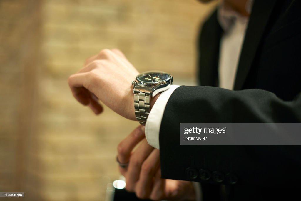 Close up of businessman fastening wristwatch : Stock Photo