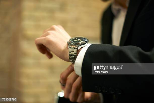 Close up of businessman fastening wristwatch