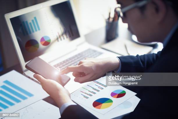 close up of businessman hand working on smartphone and laptop computer with financial business graph information diagram