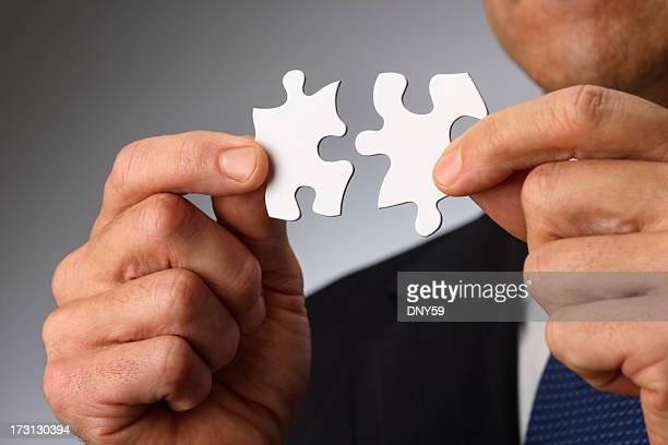 ビジネスマンのクローズアップを一緒に 2 つのパズルのピースを