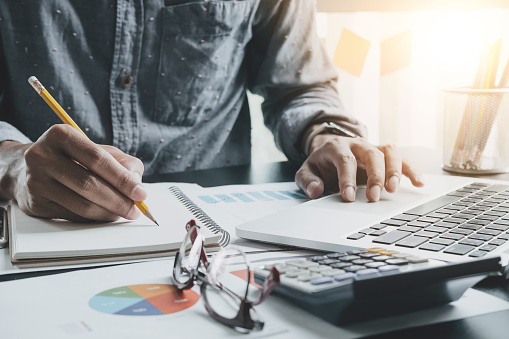 Close up of businessman or accountant hand holding pen working making notes and using laptop computer to calculate business data, accountancy document at his office, business accounting concept 905049450