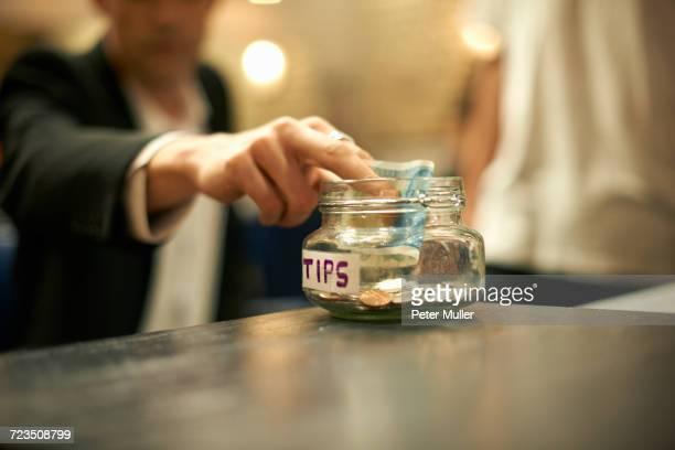 Close up of businessman putting cash into barber shop gratuity jar