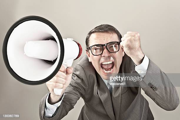 Close up of businessman screaming through megaphone against grey background