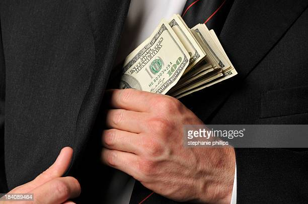 Close Up of Businessman Slipping Cash into His Suit Jacket