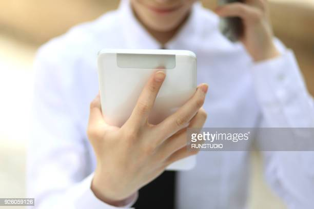Close up of businessman talking on smartphone with digital tablet outdoors