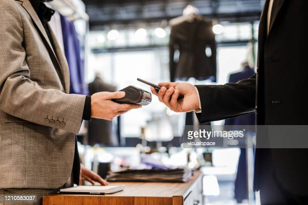 close up of businessman using smartphone to pay for shopping - nfc stock pictures, royalty-free photos & images