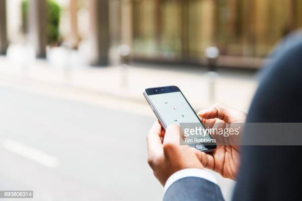 close up of businessman using taxi app - black hand holding phone stock pictures, royalty-free photos & images