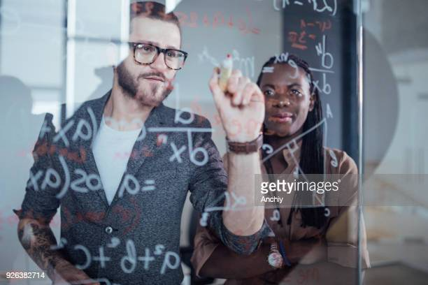 close up of businessman writing down math formulas - mathematics stock pictures, royalty-free photos & images