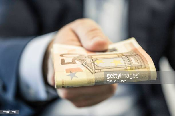 close up of businessmans hand handing folded fifty euro notes - corruption stock pictures, royalty-free photos & images