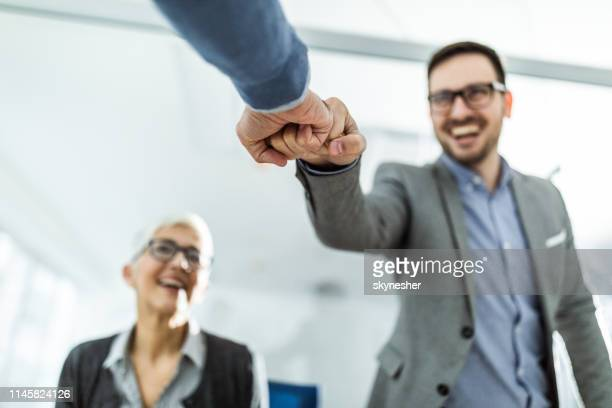 close up of businessmen fist bumping in the office. - fist bump stock pictures, royalty-free photos & images